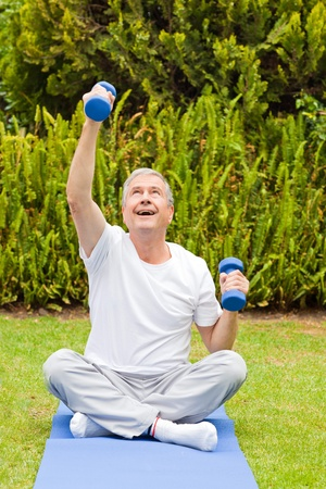 Retired man doing his exercises in the garden photo
