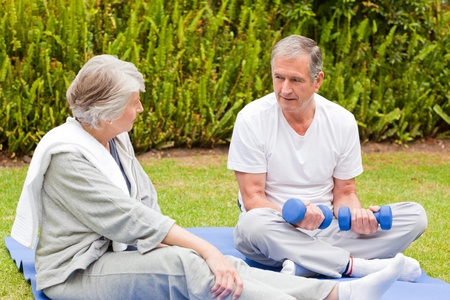 Mature couple doing their exercises in the garden Stock Photo - 10198621
