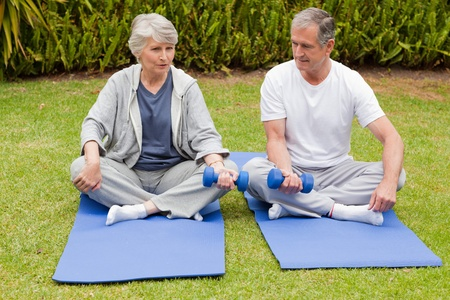 Mature couple doing their exercises in the garden photo