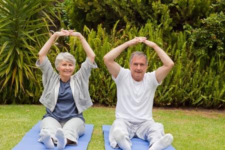 Senior couple doing their streches in the garden Stock Photo - 10205946