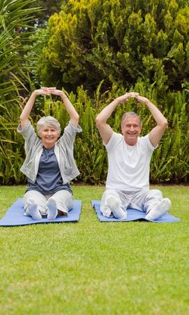 Senior couple doing their streches in the garden photo