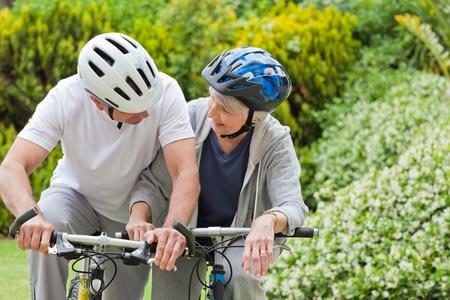 Mature couple mountain biking outside photo