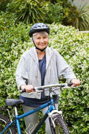Mature woman walking with her mountain bike photo