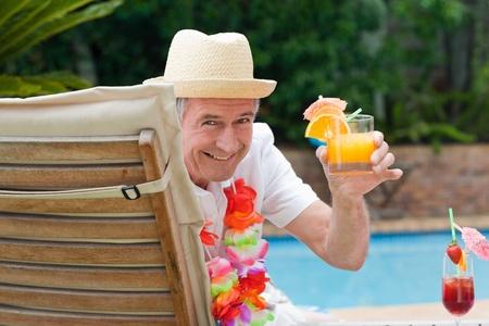 スイミング プールのそばのカクテルを飲み、成熟した男