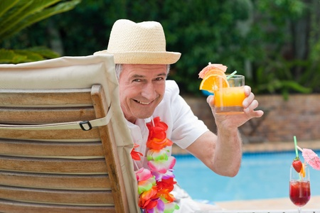 beside: Mature man drinking a cocktail  beside the swimming pool Stock Photo