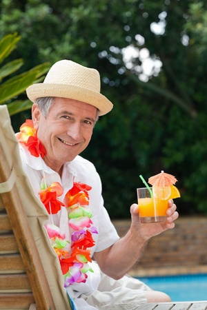 Mature man drinking a cocktail  beside the swimming pool Stock Photo - 10197535