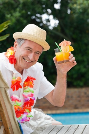 Mature man drinking a cocktail  beside the swimming pool photo
