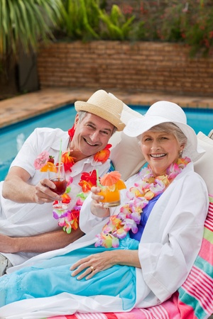 Mature couple drinking a cocktail  beside the swimming pool Stock Photo - 10197795