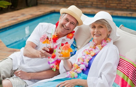 Mature couple drinking a cocktail  beside the swimming pool photo