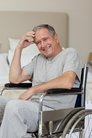 amputation: Smiling senior man in his wheelchair  at home