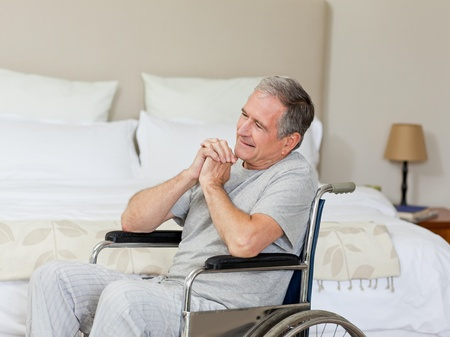 Smiling senior man in his wheelchair  at home photo