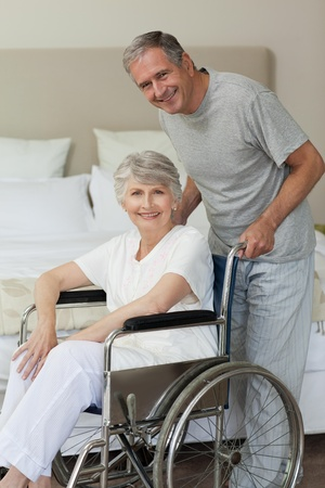 amputation: Retired woman in her wheelchair with her husband Stock Photo