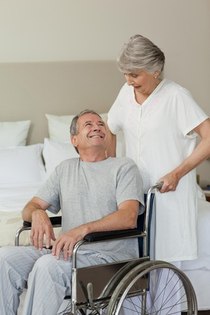 Retired man in his wheelchair with his wife photo