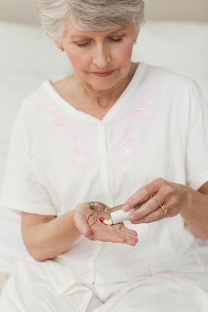 Sick senior woman taking her pills photo