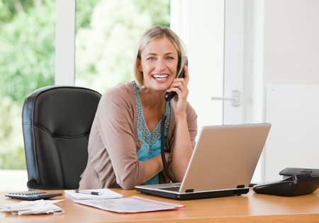 Woman working on her computer while she is phoning photo