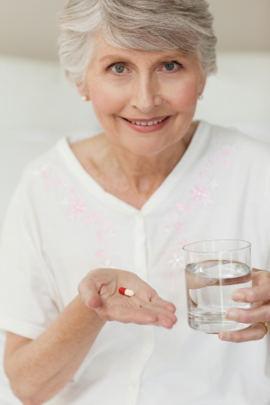 medicine bottle: Senior woman looking at the camera