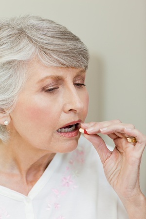 swallowing: Sick senior woman taking her pills