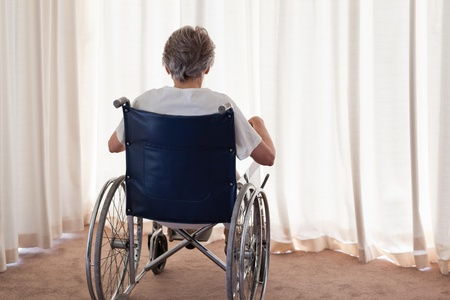 Mature woman in her wheelchair with her back to the camera at home photo