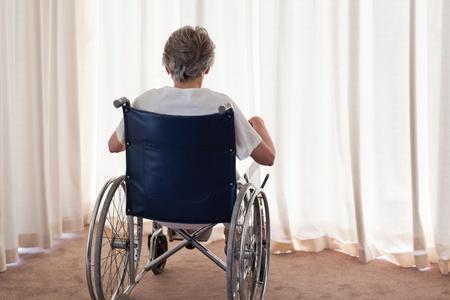 Reife Frau in ihrem Rollstuhl mit dem R�cken zur Kamera zu Hause