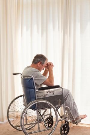handicap: Uomo riflessivo nella sua sedia a rotelle