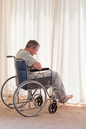 persona en silla de ruedas: Hombre pensativo en su silla de ruedas