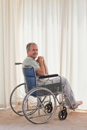 Smiling man in his wheelchair at home photo