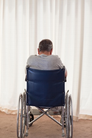 amputation: Mature man in his wheelchair with his back to the camera Stock Photo