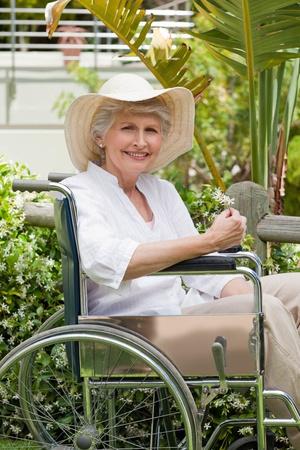 disability insurance: Donna matura nella sua sedia a rotelle in giardino