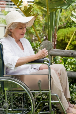 Reife Frau in ihrem Rollstuhl im Garten