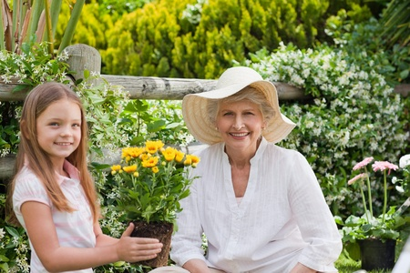 Grandmother with her granddaughter working in the garden photo