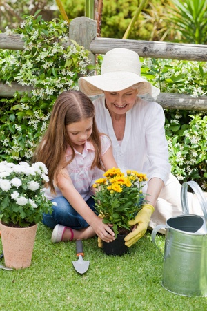 watering pot: Grandmother with her granddaughter working in the garden