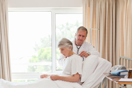 Senior doctor taking the heartbeat of his patient Stock Photo - 10194614