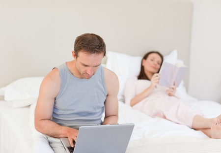 Manworking on his laptop while his wife is reading a book on the bed  photo