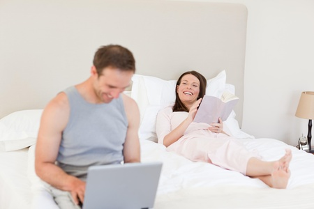 Manworking on his laptop while his wife is reading a book on the bed Stock Photo - 10192538