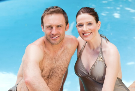 Couple looking at the camera beside the swimming pool photo