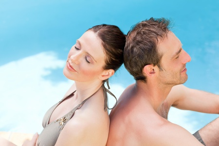 Couple sitting beside the swimming pool back to back photo