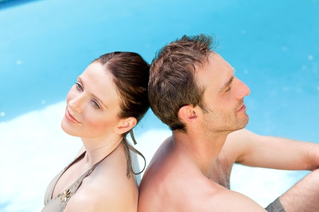 Couple sitting beside the swimming pool back to back Stock Photo - 10195866