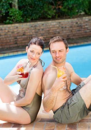 Couple drinking cocktails back to back photo