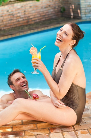 Smiling couple drinking cocktails photo