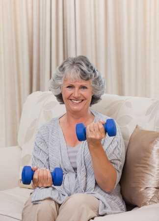 Woman doing her exercises on her sofa Stock Photo - 10195111