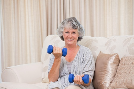 Woman doing her exercises on her sofa photo