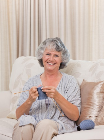 Retired woman knitting at home photo