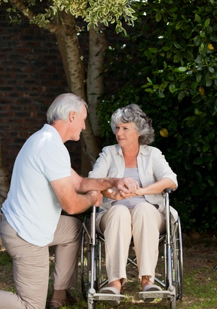 woman chair: Mature couple in the garden Stock Photo