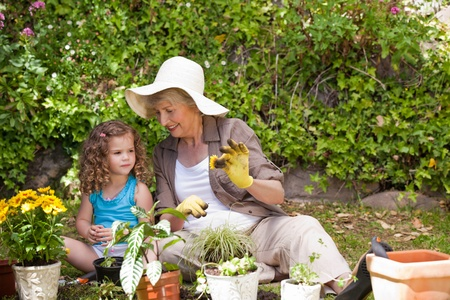 Happy Grandmother with her granddaughter working in the garden photo