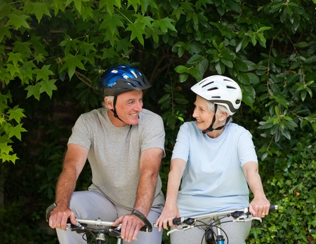 Senior couple mountain biking outside photo