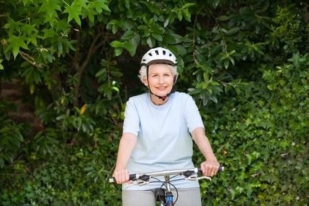 Mature woman mountain biking outside photo
