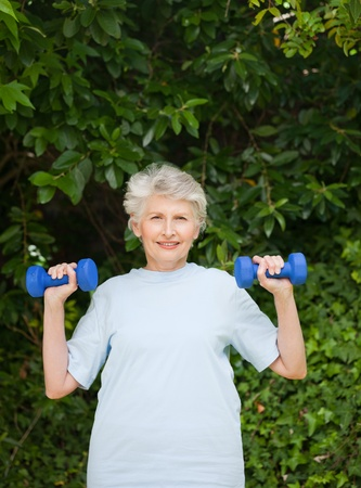 Mature woman doing her exercises in the garden photo