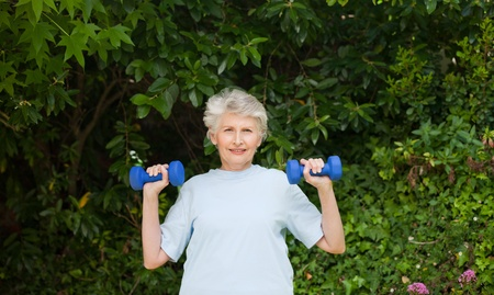Mature woman doing her exercises in the garden Stock Photo - 10197479