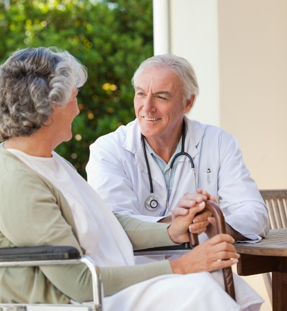Senior doctor talking with his mature patient photo
