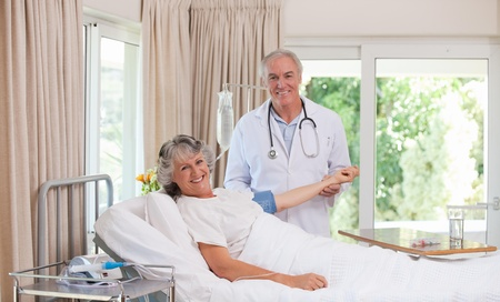 Senior doctor taking the blood pressure of his patient Stock Photo - 10195249